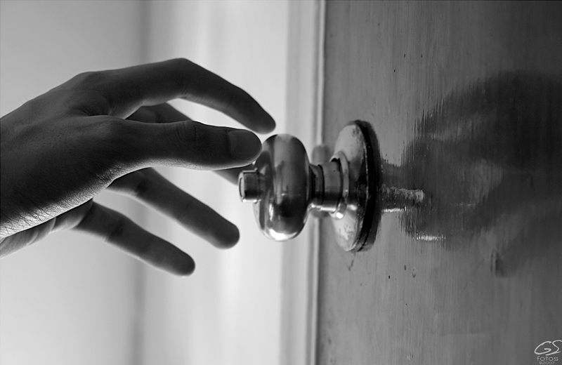 Hand reaching for a door handle (B/W)
